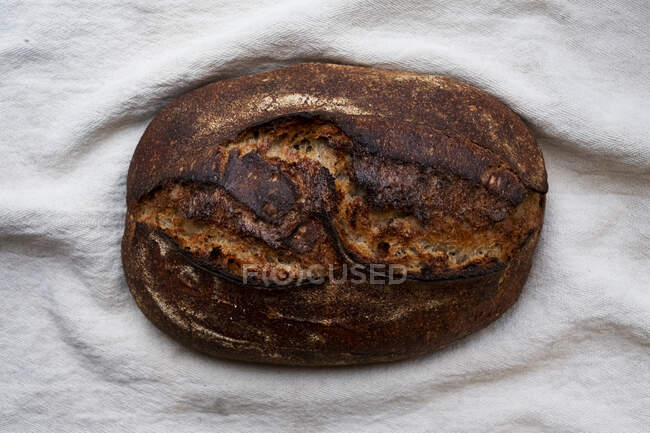High angle close up of freshly baked loaf of bread in an artisan bakery. — Stock Photo