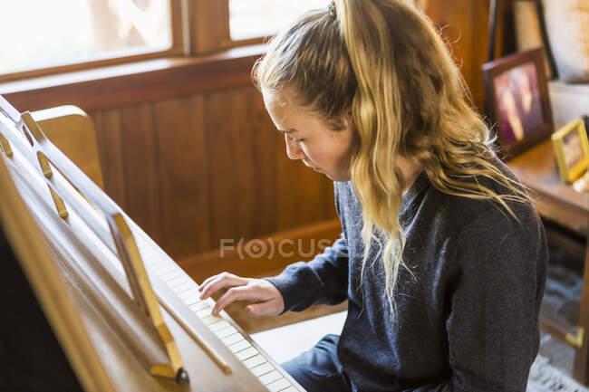 Дівчинка - підліток грає на піаніно.. — стокове фото