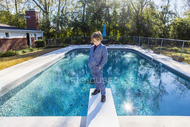 Niño de 6 años parado en el trampolín con vistas a la piscina - foto de stock
