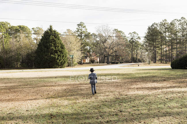 Rear view of young boy dressed in suit walking on lawn — Stock Photo