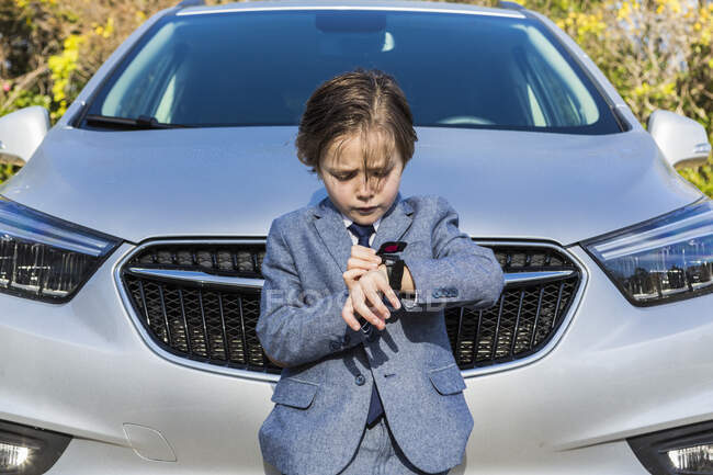 6 year old boy leaning on car, looking at his watch — Stock Photo