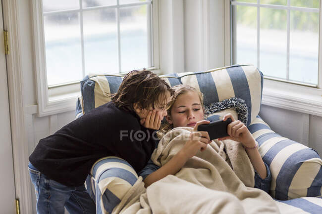 Boy and a teenage girl looking at the screen of a smart phone. — Stock Photo