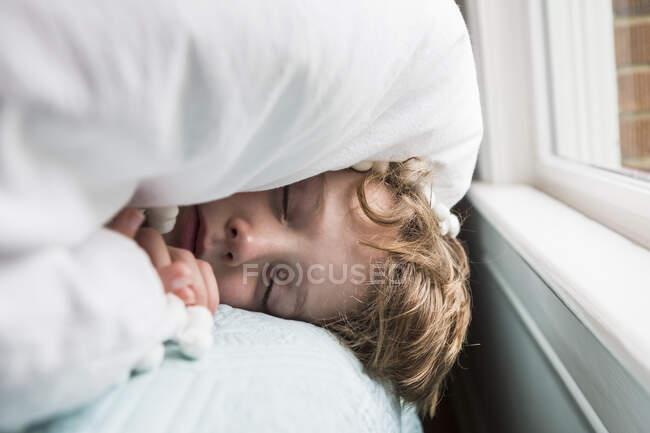 6-летний мальчик в кровати с покрывалом на голове — стоковое фото