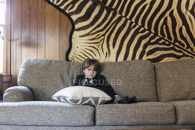 6-jähriger Junge sitzt auf Sofa — Stockfoto