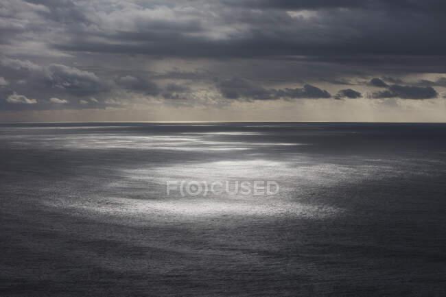 Nuvens tempestades limpando sobre o oceano expansivo, luz solar sobre a água, costa norte de Oregon — Fotografia de Stock