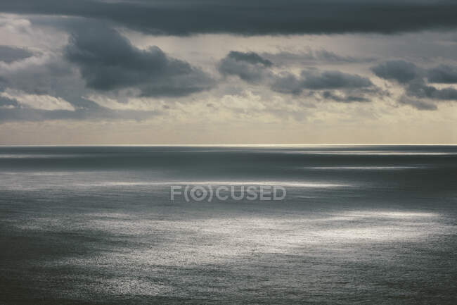 Nuages orageux s'éclaircissant au-dessus d'un vaste océan, lumière du soleil sur l'eau, côte nord de l'Oregon — Photo de stock