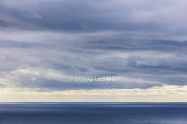 Storm clouds clearing over expansive ocean, dappled sunlight on water, northern Oregon coast — Stock Photo