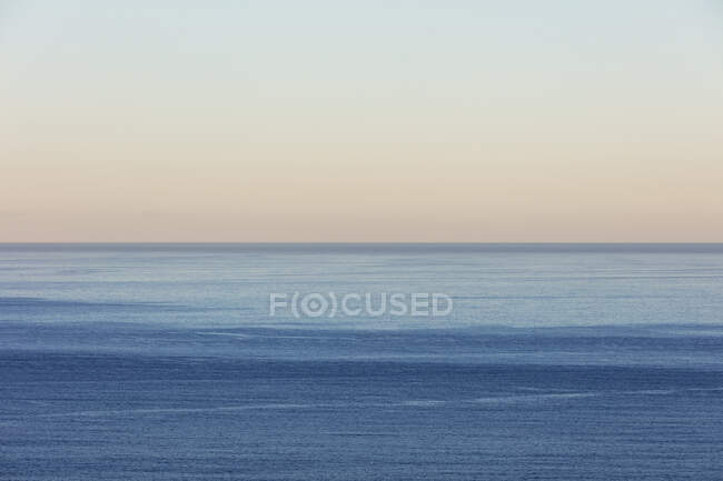 View of calm ocean water, horizon and sky at dawn, northern Oregon coast — Stock Photo