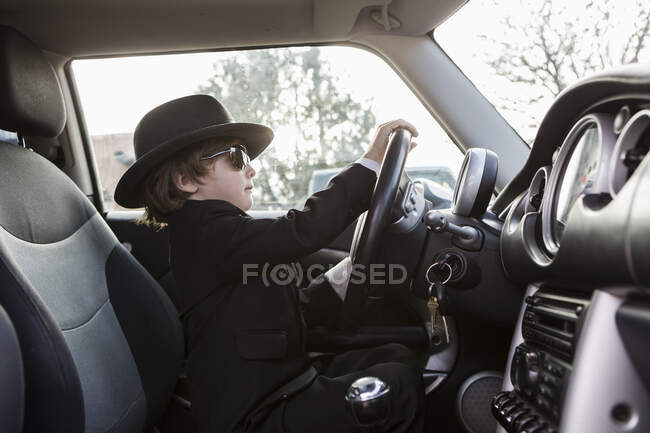 6 year old boy sitting in car holding steering wheel — Stock Photo