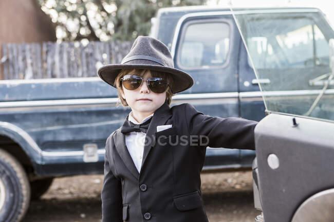 Garçon de 6 ans penché sur la porte de voiture ouverte — Photo de stock