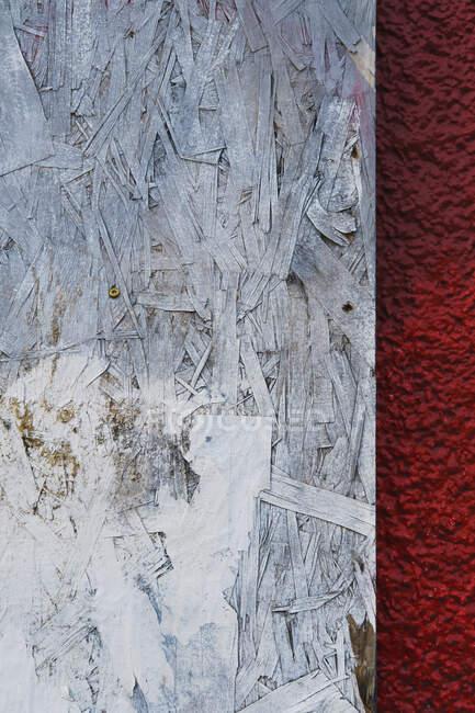 Tablero de partículas blanco pintado contra estuco rojo - foto de stock