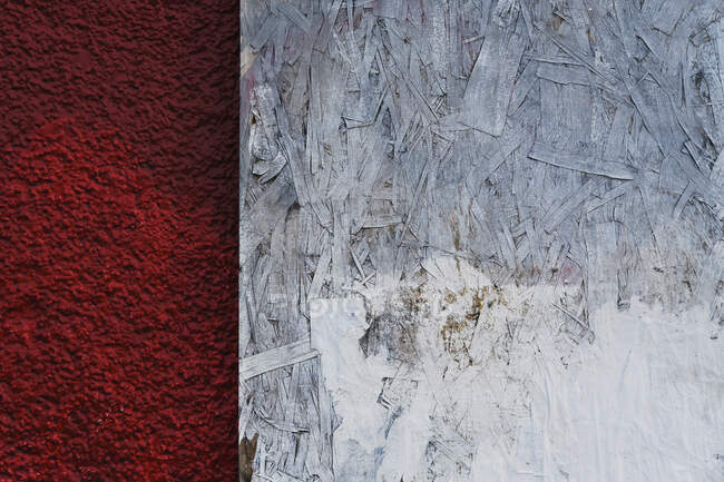 Painted white particle board against red stucco — Stock Photo