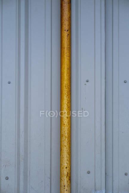 Помаранчевий жолоб проти металевої стінки зі сховища. — стокове фото