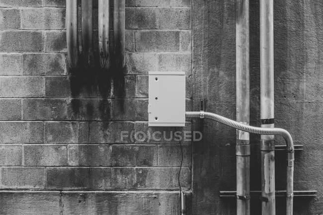 Tuyauterie électrique métallique sur le mur du bâtiment — Photo de stock