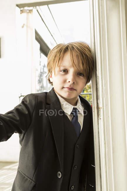 Портрет 6-летнего мальчика, открывающего дверь — стоковое фото