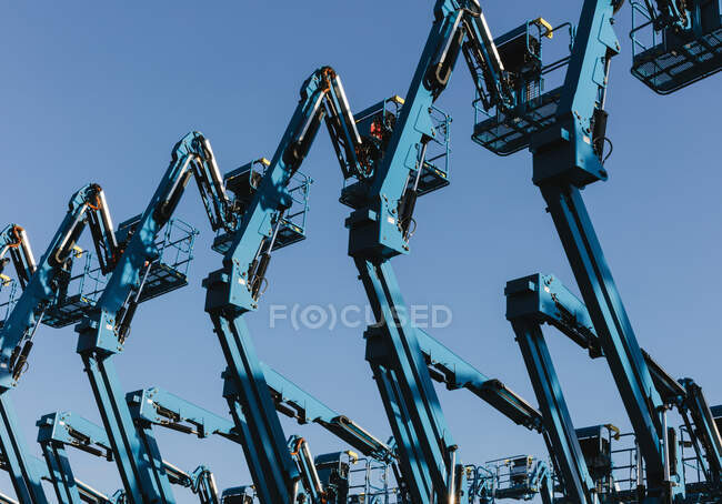Row of hydraulic mobile cherry picker platforms at outdoor storage facility — Stock Photo