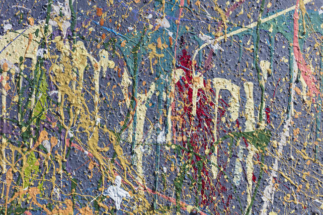 Close-up view of colorful graffiti paint splatters on urban wall, abstract background — Stock Photo