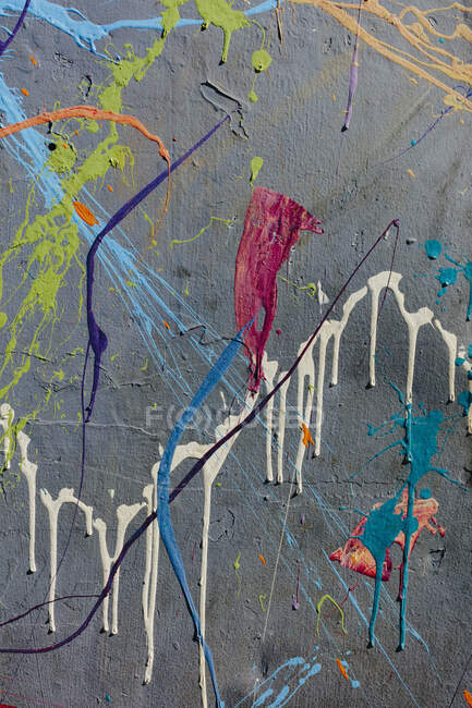 Colorful graffiti paint splatters on urban wall — Stock Photo
