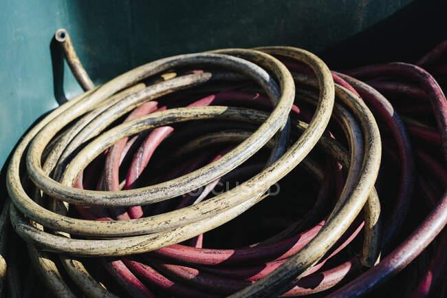 Pilha de tubos industriais descartados, enrolada em recipiente de reciclagem — Fotografia de Stock