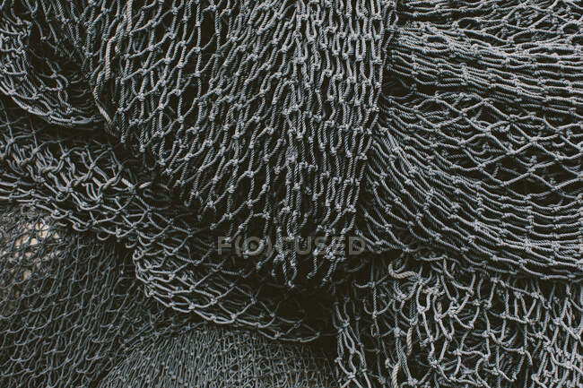 Close-up view of pile of commercial fishing nets and gillnets on a fishing quay — Stock Photo