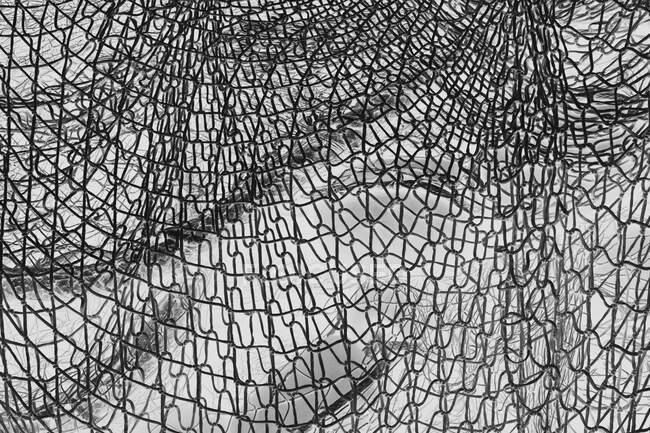 Immagine invertita in bianco e nero di reti da pesca e funi commerciali su banchina da pesca. — Foto stock