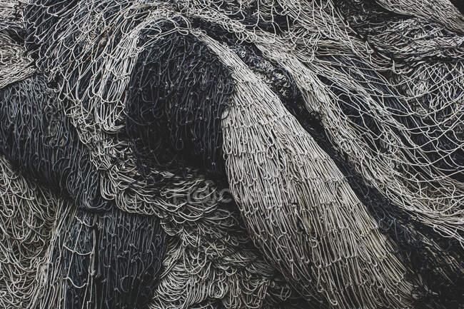 Pile de filets de pêche commerciale et de filets maillants sur un quai de pêche — Photo de stock