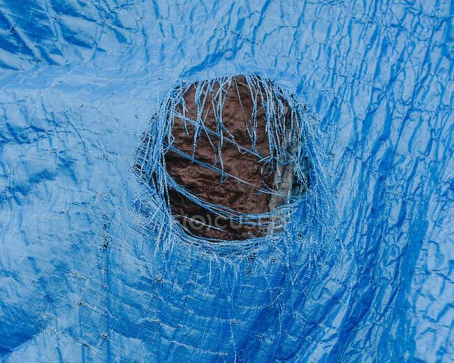 Закритий зношений синій брезент з розірваною ямою в центрі. — стокове фото