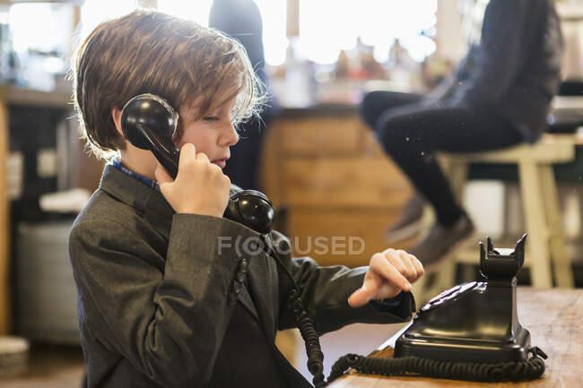 Niño de seis años en un traje hablando en un viejo teléfono vintage en casa - foto de stock