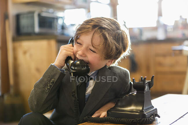 Six year old boy in a suit and tie talking on a old vintage phone at home — Stock Photo