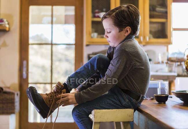Garçon de six ans portant ses bottes, assis sur un tabouret haut . — Photo de stock