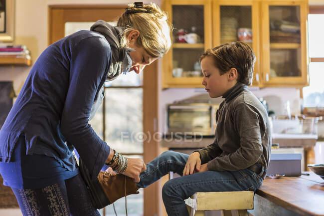 Mère mettre des bottes sur son fils de six ans au petit matin — Photo de stock