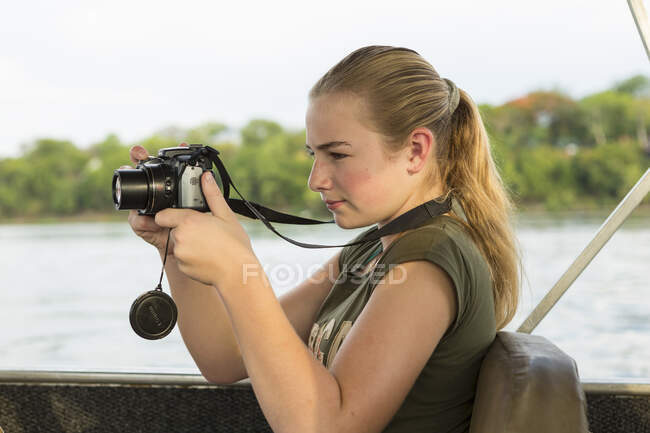 A twelve year old girl using a camera seated in a river boat. — Stock Photo
