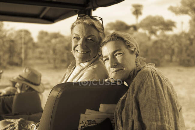 Senior woman and mature daughter, two generations of women in a safari vehicle laughing. — Stock Photo