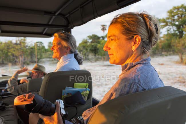 Donna anziana e figlia matura, due generazioni di donne in un veicolo safari che guardano al tramonto. — Foto stock
