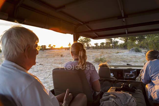 Три поколения семьи на сафари, в автомобиле на закате. — стоковое фото