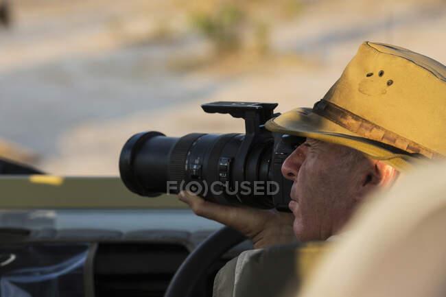 Мужчина в шляпе с длинным объективом. — стоковое фото