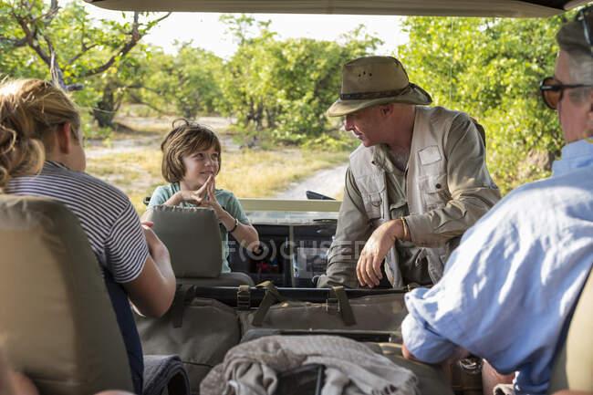 Eine Familie von Besuchern in einem Safari-Fahrzeug mit einem Führer. — Stockfoto