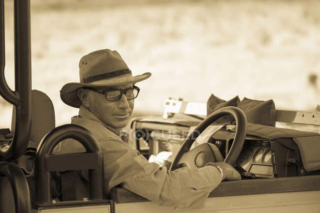 Uomo maturo con cappello e occhiali sul sedile di guida di un veicolo, tono seppia. — Foto stock