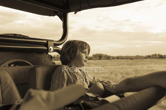 Ragazzo di cinque anni seduto in un veicolo safari, monocromatico. — Foto stock