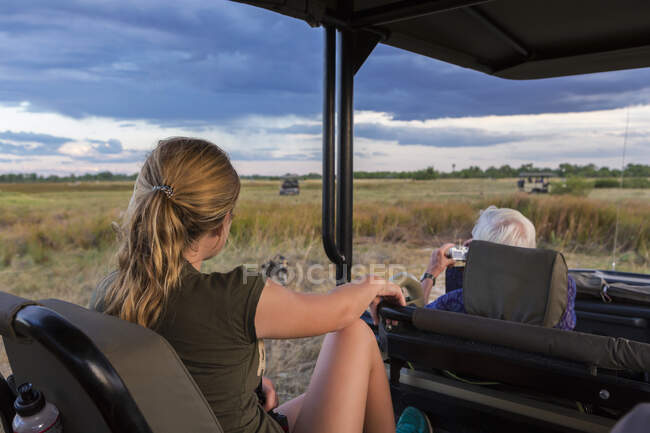 Adolescente y hombre mayor sentado en un vehículo de safari observando una manada de perros salvajes. - foto de stock