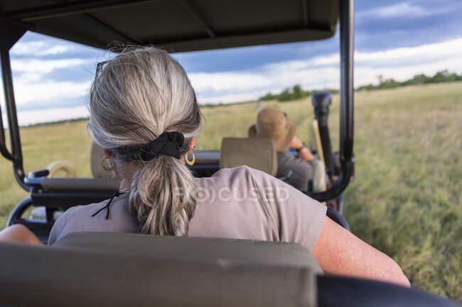 Donna con i capelli grigi seduta in un veicolo safari, osservando la fauna selvatica — Foto stock