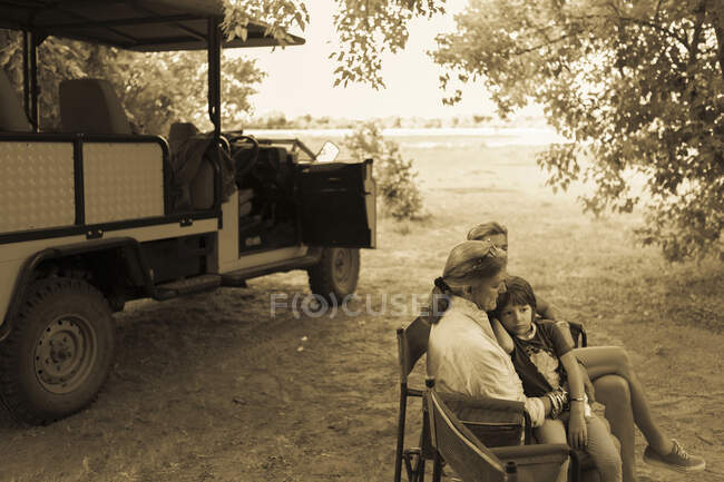 Three generations of a family seated in folding chairs by a safari jeep, under trees, monochrome. — Stock Photo