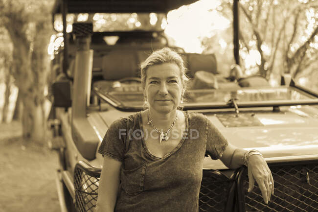 Portrait of woman leaning on a safari vehicle — Stock Photo
