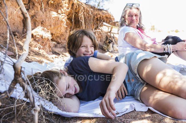 Trois personnes, grand-mère et deux enfants se reposant à l'ombre pendant une randonnée — Photo de stock