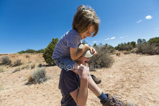 14 year old girl giving younger brother a piggyback ride, Galisteo Basin, NM. — Stock Photo