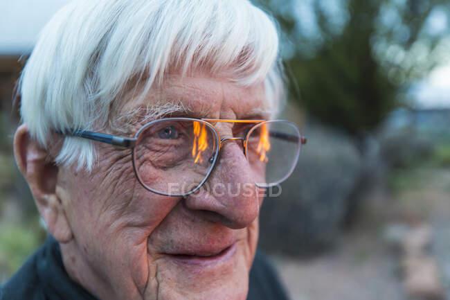 Крупный план старшего улыбается, и пламя отражается в его очках — стоковое фото
