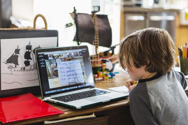 Un enfant travaillant à la maison, leçons en ligne pendant le confinement — Photo de stock