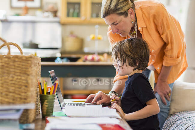 Adult woman helping her six year old son with a remote learning session on a laptop, using a touch pad. — Stock Photo