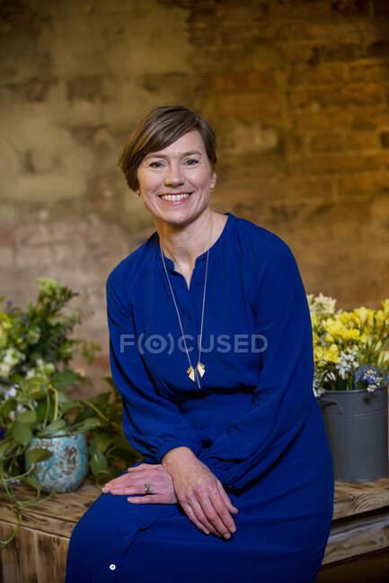 Ritratto di una donna celebrante di cerimonia di nomina vestita di blu, sorridente alla macchina fotografica. — Foto stock