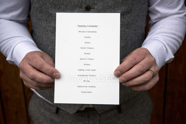 Close up of man holding order of service for a naming ceremony. — Stock Photo